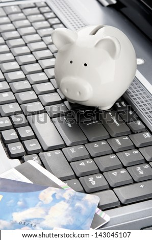 Piggy bank and credit cards over a laptop keyboard as a symbol of internet banking