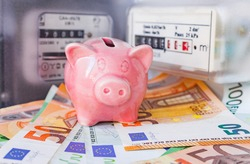 Piggy bank and Euro cash near an electricity meter and gas meter. Utility bills, consumption of electricity and gas for heating home, energy costs, symbolic image.