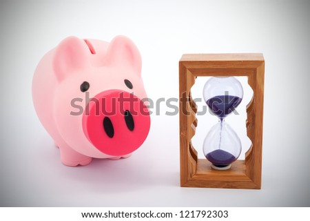 Piggy bank and hourglass objects on white background