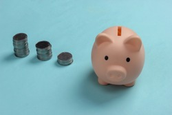 Piggy bank and stack of coins on blue background, saving money, wealth and financial for investment