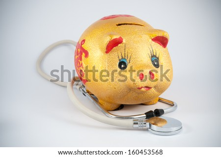 Piggy bank and stethoscope on white background