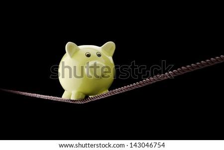 Piggy bank balancing on tightrope
