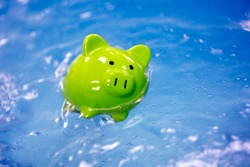 Piggy bank drowning in debt sinking in water concept for bankruptcy and business financial crisis