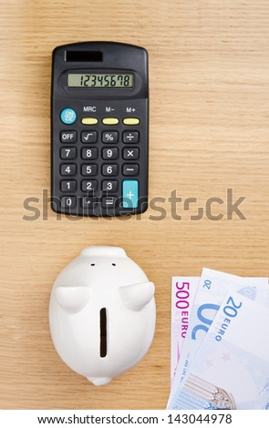 Piggy bank, euro bills and calculator on a table. Top view.