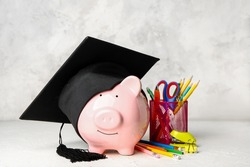 Piggy bank, graduation hat and stationery on table. Tuition fees concept