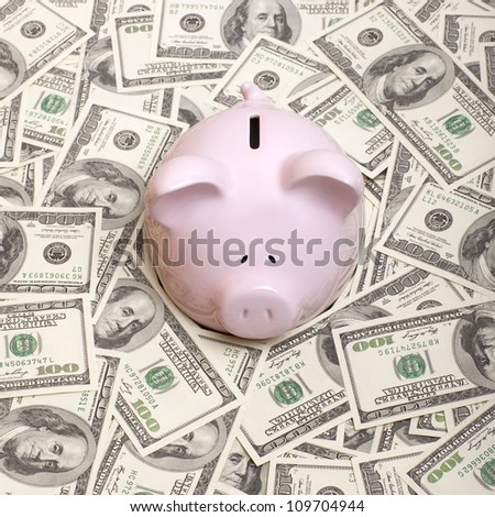 Piggy bank in a pile of dollars
