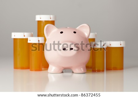 Piggy Bank In Front of Several Medicine Bottles on a Gradated Background. - stock photo