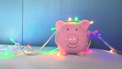 piggy bank in light decoration blue blank background. Christmas or Newyear celebration, saving money for spending on holiday vacation. happy new year lifestyle of people in 2021. financial business