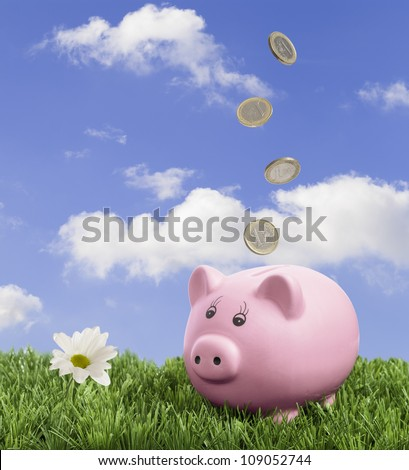 Piggy bank in the grass with falling Euro coins