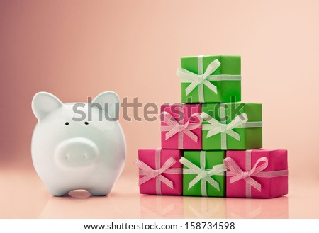 Piggy bank next to a gift boxes stack