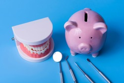 Piggy Bank on a blue background and dental instruments. The concept of saving money for the manufacture of dental implants and treatment.
