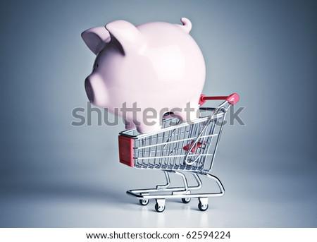 Piggy bank on a miniature shopping cart