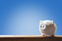 Piggy bank on blue background. Soft focus