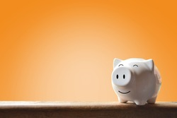 Piggy bank on orange background. Soft focus