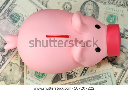 Piggy bank on paper money dollar pile