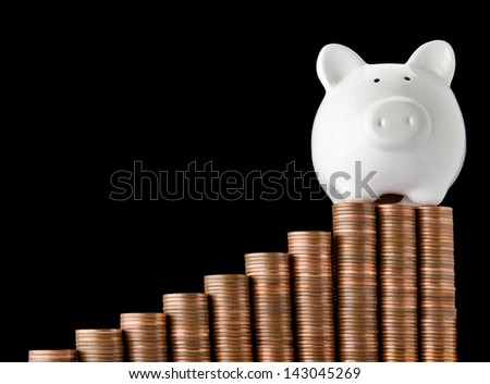 Piggy bank on top of stack of coins showing growth