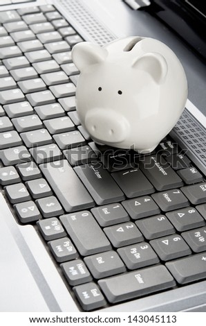 Piggy bank over a laptop keyboard as a symbol of technology and information cost or internet banking