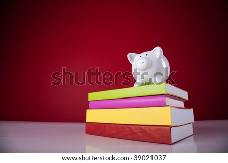 piggy bank over a stack of colorful books with a red background