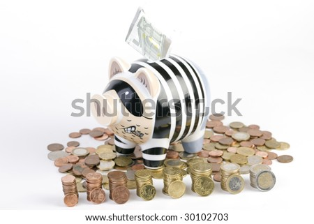 Piggy bank sitting on Euro coins with 5 Euro banknote and on foreground batched euro coins