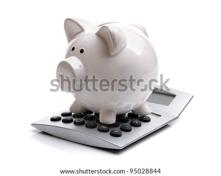 Piggy bank sitting on top of a calculator concept for calculating finance