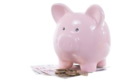 Piggy bank standing on a pile of UK money with pound banknotes and coins isolated on white in a financial concept with copy space