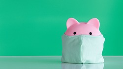 Piggy bank to prevent COVID-19 mask On a green background.