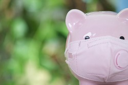 Piggy bank wearing a mask in front of green background