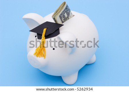 Piggy bank with a graduation cap on blue background
