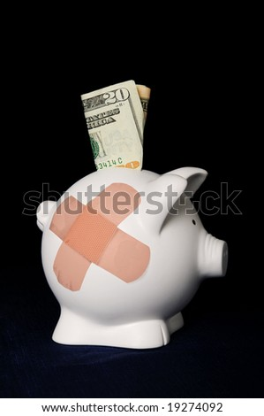Piggy bank with bandages over a dark background - stock photo