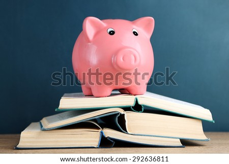 Piggy bank with books on blackboard background #292636811