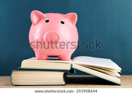 Piggy bank with books on blackboard background #292908644