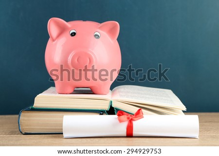 Piggy bank with books on blackboard background #294929753