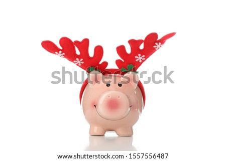 Piggy bank with Christmas deer horns isolated on white background