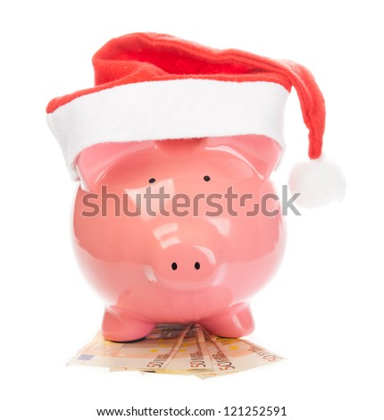 Piggy bank with christmas hat standing on euros.