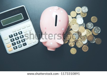 Piggy bank with coins and calculator on dark table