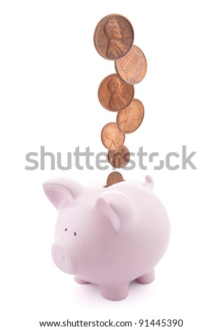 Piggy bank with coins falling into slot