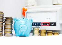 Piggy bank with coins near the natural gas meter at home. The symbolic image of the high cost of natural gas for heating homes in the cold season. Selective focus.