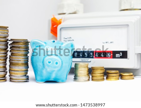 Piggy bank with coins near the natural gas meter at home. The symbolic image of the high cost of natural gas for heating homes in the cold season. Selective focus. #1473538997
