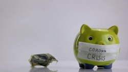 Piggy bank with facial mask for corona crisis. Rumpled dollar banknote. Isolated on white background.