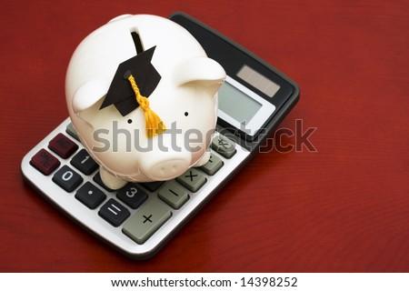 Piggy bank with graduation cap and calculator