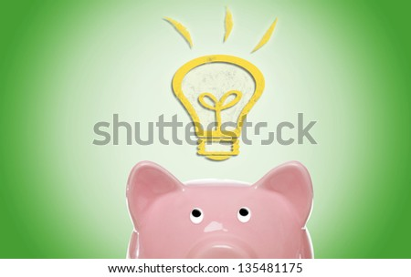 Piggy bank with idea light bulb on green background