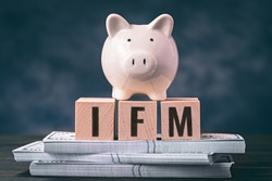 Piggy bank with IFM spelled in letters on wooden blocks and bundles of banknotes. International Monetary Fund metaphor