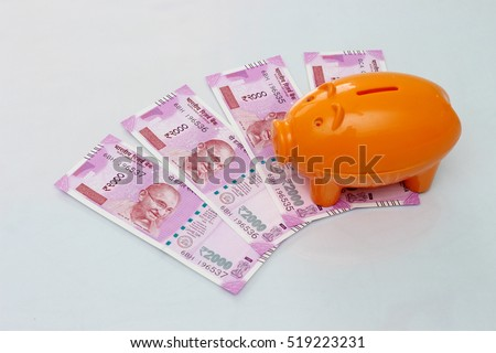 Piggy bank with new 2000 rupee notes on white background.