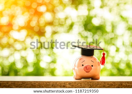 Piggy bank with saves with wear graduation cap put on the table on bokeh background in the public park, Planning for education in the future concept.