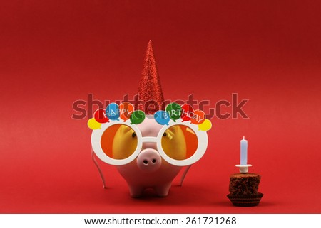 Piggy bank with sunglasses Happy birthday, party hat and birthday cake with blue candle on red background
