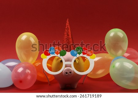 Piggy bank with sunglasses Happy birthday , party hat and multicolored party balloons on red background