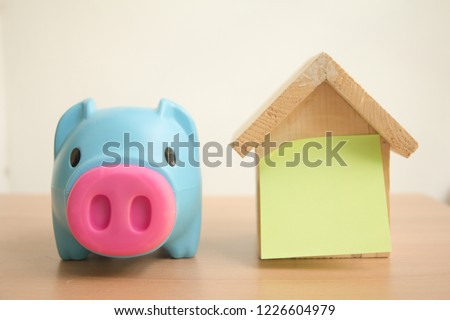 Piggy bank with wood house model and sticky paper note for write your text. #1226604979