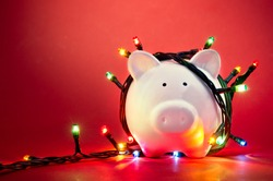 Piggy bank wrapped in Christmas string lights