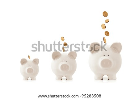 Piggy banks increasing in size, with coins falling into them.  Growing investment concept.