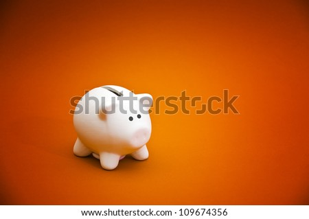 Piggy coin bank on orange background. Cute white ceramic piggy coin bank for money savings, financial security or personal funds concept.